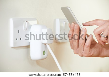 Woman Controlling Smart Plug Using App On Mobile Phone