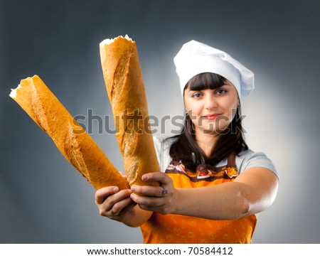 woman cook holding broken  french bread, focus on the bread
