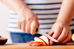 Woman cooking and cutting apple on wooden cutting board. Preparing healthy food. Hands holding knife and slicing fruits on table in kitchen