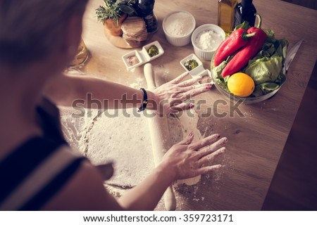 Woman cooking healthy balanced food.Carbohydrates.Whole grains.Dieting.Cooking food at home.Woman preparing dough on wooden table in the kitchen.Rolled out dough on table with rolling pin.Pizza crust