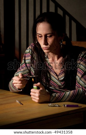 Woman cooking heroin in a bent spoon - stock photo