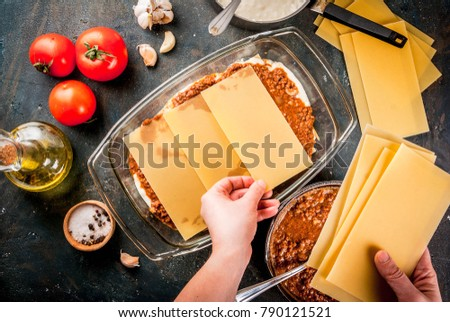 Woman cooking homemade classic lasagna bolognese, on dark blue table; with ingredients, top view copy space, hands in picture
