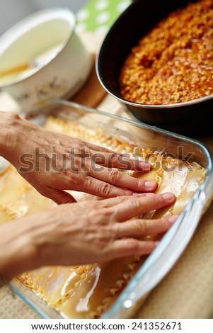 Woman cooking lasagna, arranging the pasta in a tray with filling