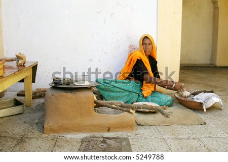 Woman cooking naan bread in courtyard, Rajasthan, India