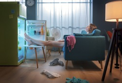 Woman cooling herself in front of the open fridge at home during the summer, she is sitting on the sofa with feet up