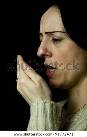 woman coughing, sneezing into hand black background - stock photo
