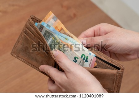 Woman counting different euro banknotes in her leather purse #1120401089