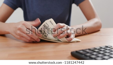 Woman counting Japanese banknote