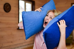 woman covered ears with pillow. Noisy neighbors make it difficult to live peacefully. woman was tired of loud neighbors and covered ears. Harmful neighbors.
