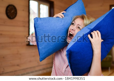 woman covered ears with pillow. Noisy neighbors make it difficult to live peacefully. woman was tired of loud neighbors and covered ears. Harmful neighbors. ストックフォト ©