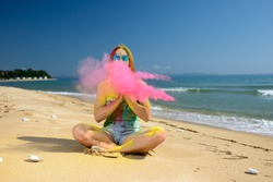 woman covered with holi paint on sea shore