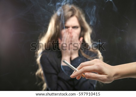 Woman covering face from cigarette smoke. Passive smoking concept