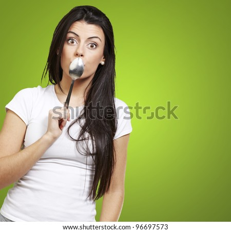 woman covering her mouth with a spoon against a green background