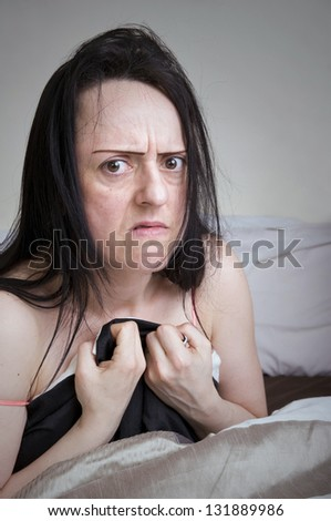 woman covering herself with bed sheets in bedroom looking disgusted