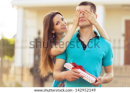 woman covering man's eyes hands. man with gift