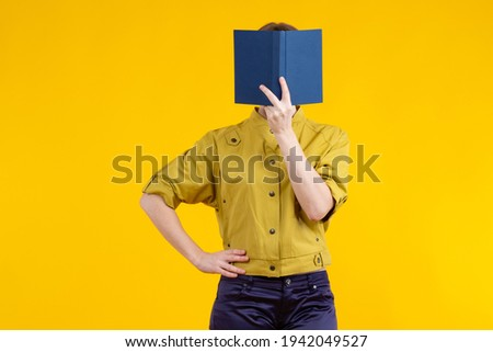 Woman covers her face with a book. Portrait of a girl without a face. Concept - selling books. Literature store. Girl with a book on a yellow background.  Woman reading a book while standing