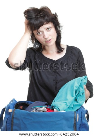 woman crammed full of clothes in black and blue shoulder bag isolated on white