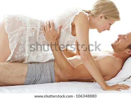 Woman crawling over man in bed, being playful and smiling.