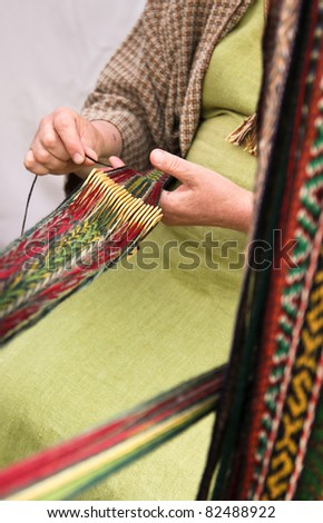 Woman crocheting pattern stripes with traditional tool