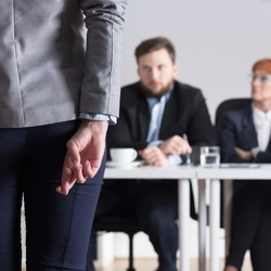 Woman crossing fingers during jobinterview and three businesspeople
