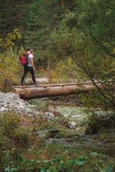 Woman crossing precarious wooden log bridge over the Karwendelbach river in the Karwendel Alps, Tirol, Austria