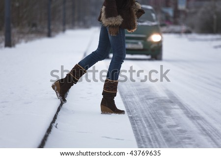 woman crossing the snowy road before car