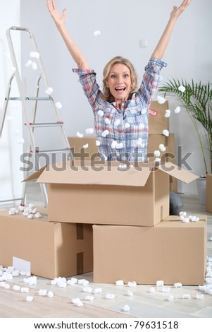 Woman crouching in front of stacked cardboard boxes