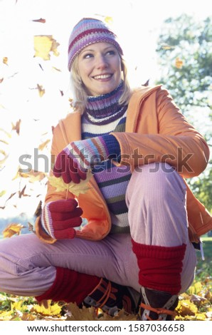 Woman crouching outdoors among falling leaves, autumn