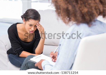 Woman crying on sofa during therapy session while therapist is taking notes