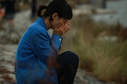 Woman crying on the riverbed