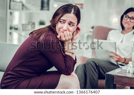 Woman crying. Overemotional woman crying while sharing problem about breakup with smart therapist #1366176407
