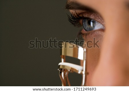 Woman curling her eyelashes looking off into the distance
