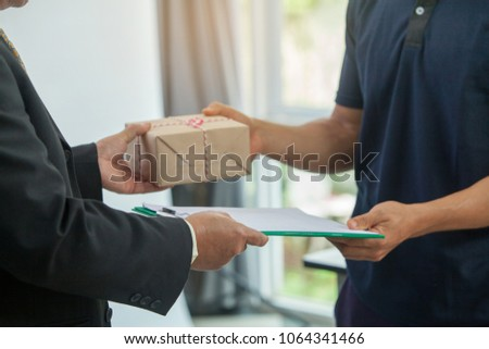 Woman Customer hand Accepting Receiving a package  from a Deliveryman in blue uniform at home. postal and delivery package through a Service,courier Service concept,