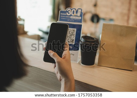 woman customer using digital mobile phone scan QR code pay for buying coffee in modern cafe coffee shop, cafe restaurant, digital payment, online shopping, takeaway food, internet technology concept