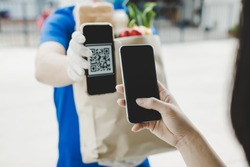 woman customer using digital mobile phone scan QR code paying for buying fresh food set bag from food delivery service man, express delivery, digital payment technology and fast food delivery concept