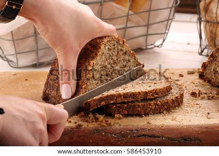 Woman cut whole grain bread on a wooden board #586453910