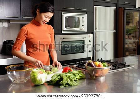 Woman cutting vegetables in kitchen, portrait