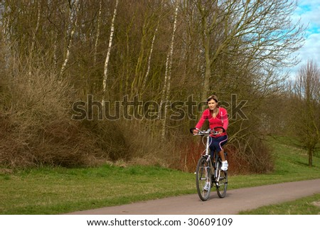 Woman cycling in a park.