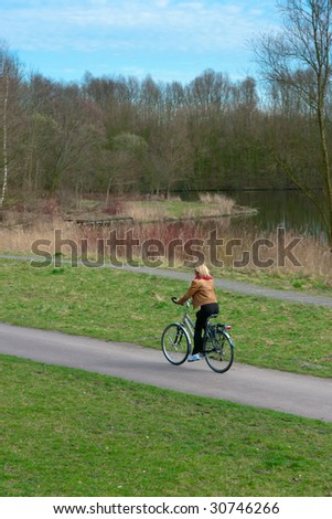 Woman cycling in a park along a lake.