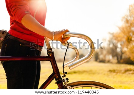 Woman cycling on bicycle, sunset autumn park exercising. Take a bike for a walk, vintage old retro bike, cycling or commuting in rural country environment, ecological transportation concept