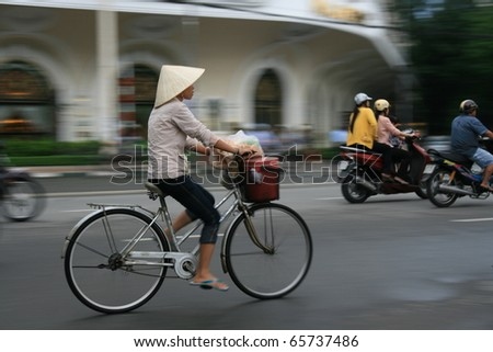 Woman cycling on busy Hanoi Roadwith traditional Vietnamese hat