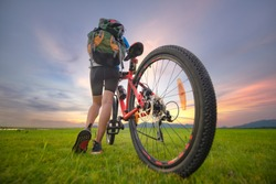 Woman cyclist bicycle riding on the way of meadow field, adventure woman riding mountain bike alone in meadow at countryside