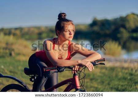 woman cyclist. dreams on the lake. troubled future