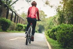 Woman cyclist riding a bike on sunny park trail in spring