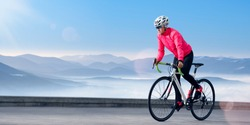 Woman Cyclist Riding Road Bike on the Mountain Road at Sunny Morning. Adventure, Travel, Healthy Lifestyle and Sport Concept.