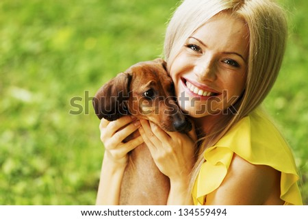 woman dachshund in her arms on grass