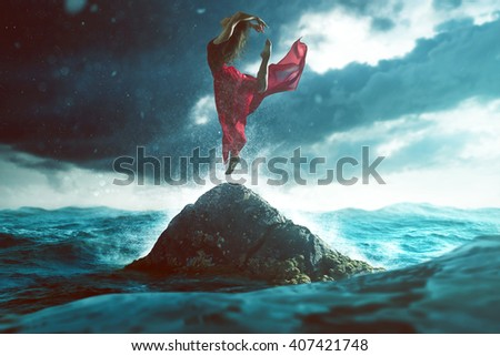 Woman dances on a rock in the sea