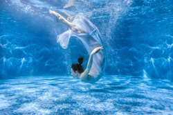 Woman dances under the water, she is in the pool.