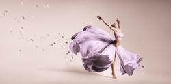 Woman dancing in flowing purple dress in studio