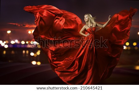 woman dancing in silk dress, artistic red blowing gown waving and flittering fabric, night city street lights #210645421